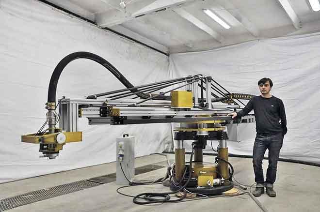 Inventor Nikita Chen-yun-tai stands alongside the <del>Terminator T2000</del> mobile 3D printer. (Photo: Apis Cor)