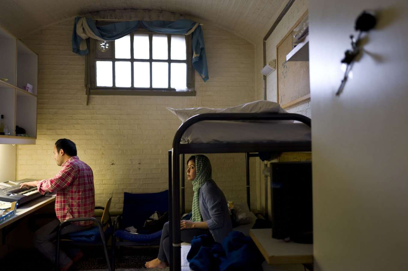 Afghan refugee Hamed Karmi, 27, plays keyboard next to his wife Farishta Morahami, 25, sitting on a bed inside their room at the former prison of De Koepel in Haarlem, Netherlands. (Photo: Jakarta Post)