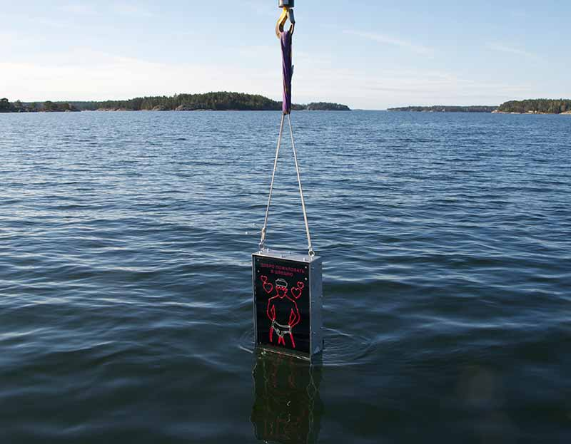 The gay singing sailor sign being lowered into the water just off Stockholm. Installed in 2015 the sign is tasked with greeting Russian submariners who may merely be passing by. (Photo: svenskafreds.se)