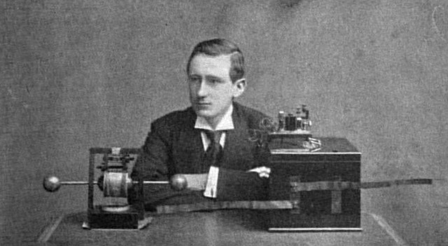 Publicity photo in a magazine of British-Italian radio entrepreneur Guglielmo Marconi with his early wireless radiotelegraphy transmitter and receiver, invented around 1895. On the left is his spark gap transmitter, consisting of a dipole antenna made of two brass rods with a spark gap between them, which transmits pulses of radio waves spelling out text messages in Morse code. On the right is his receiver, consisting of a coherer which rings a bell when it receives the dots and dashes of Morse code The bell and batteries are in the box. (Photo: Wikimedia)