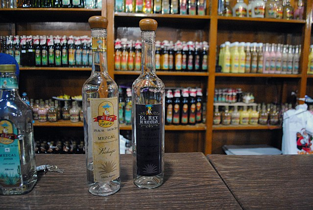Mezcal bottles at a factory in Teotitlán del Valle, Oaxaca. The more expensive the bottle of Mezcal the less likely it is to contain a worm. (Photo: Wikimedia/ProtoplasmaKid)